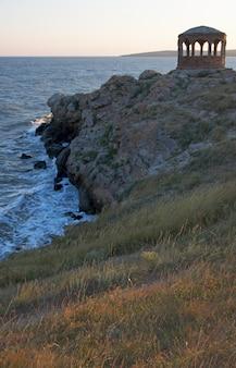 Sea surf geweldige golfpauze aan kustlijn en kaap met paviljoen op afstand
