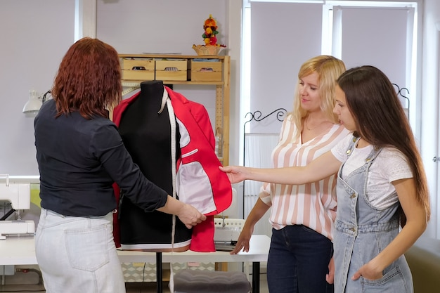 Seamster leert haar studenten om kleding te naaien, laat details zien op een jas op cursussen.