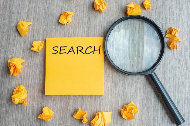 Search woorden op gele noot met verkruimeld papier en vergrootglas