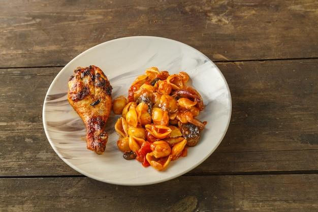 Seashell pasta in tomaat met kippenpoot gebakken op de grill op een houten tafel. horizontale foto