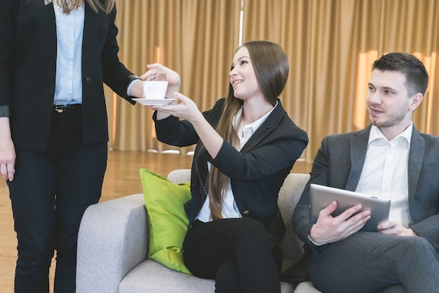 Secretaresse bracht een kopje koffie voor zakelijke bijeenkomst