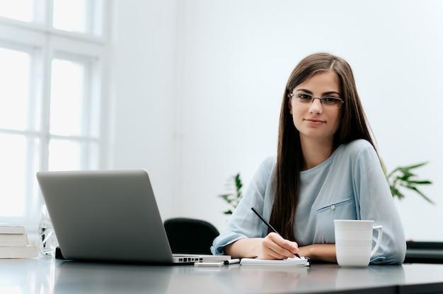Secretaresse die documenten op haar kantoor schrijft.