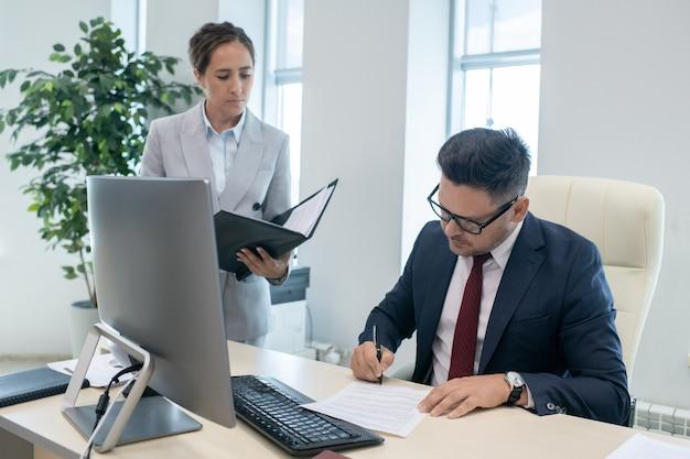 Secretaresse die haar werkgever bekijkt die contract door werkplaats ondertekent