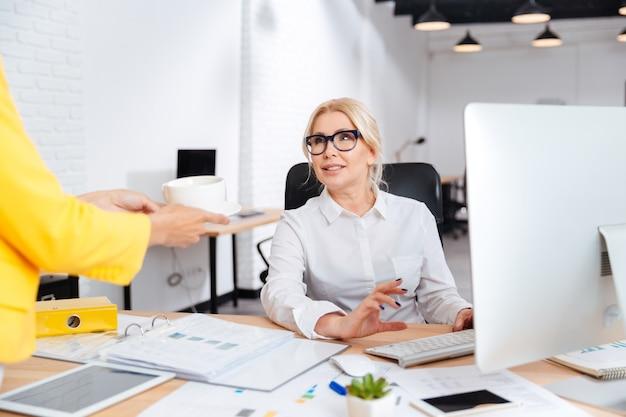 Secretaresse of collega die een welkomstkopje koffie brengt voor de lachende baas