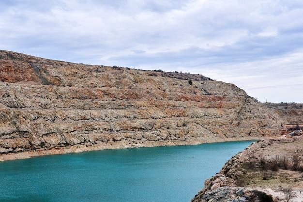 Sectie van een oude kalksteengroeve met onderaan een blauw meer