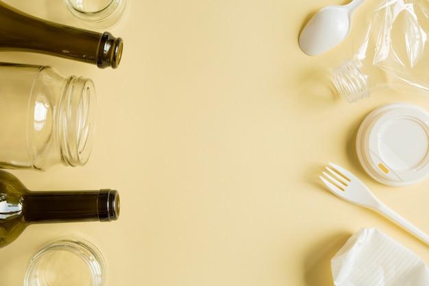 Secundair gesorteerd glas en plastic afval op de gele achtergrond. afval voor recycling bovenaanzicht op geel papier achtergrond met kopie ruimte.