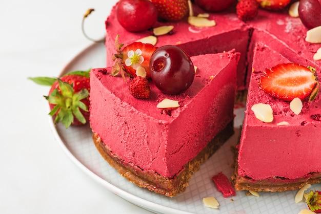 Segment van bessen vegan cheesecake of cake met verse kersen en aardbeien in een plaat. detailopname. gezond veganistisch dessert
