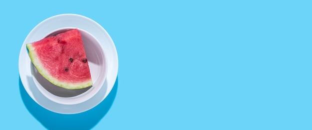 Segment van sappige rode watermeloen in een bord op een blauwe achtergrond. bovenaanzicht, plat gelegd. banier.