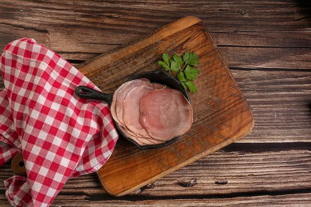 Segment van vleeswaren op een snijplank op een houten tafel