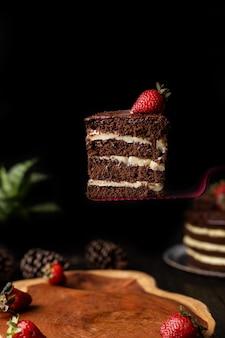 Segment van zelfgemaakte chocoladetaart met lekkere aardbeien op tafel