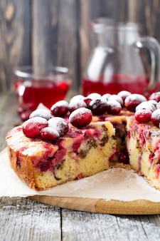 Segment van zelfgemaakte cranberry cake met walnoten, bessen en poedersuiker op de oude houten fone. ruimte voor tekst. rustieke stijl. selectieve aandacht.