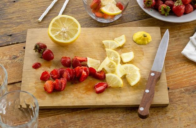 Segmenten van aardbeien en citroen op een houten bord