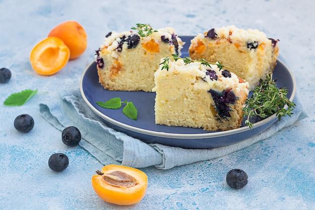 Segmenten van abrikoos en bosbessen crumble cake op blauwe keramische plaat