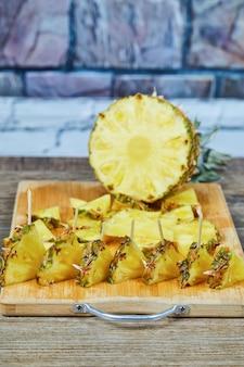 Segmenten van ananas op een houten bord.