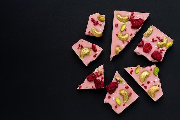 Segmenten van belgische chocolade met bessen, cashewnoten en pistachenoten