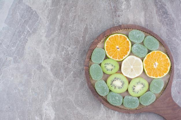 Segmenten van citrusvruchten, kiwi en snoepjes op een houten bord.