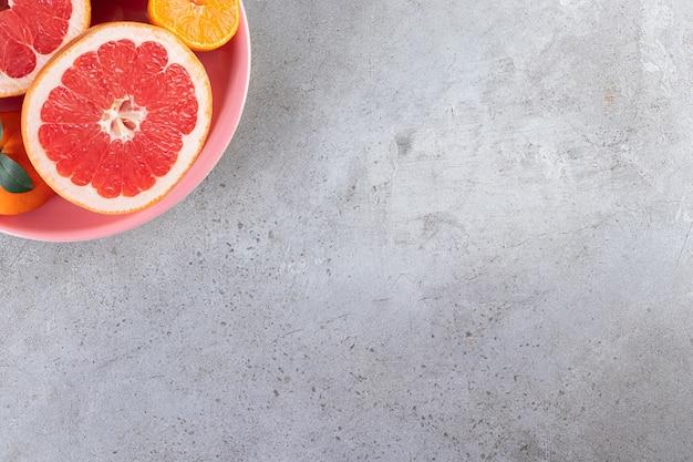 Segmenten van citrusvruchten sinaasappel en grapefruit fruit geplaatst op een roze kom