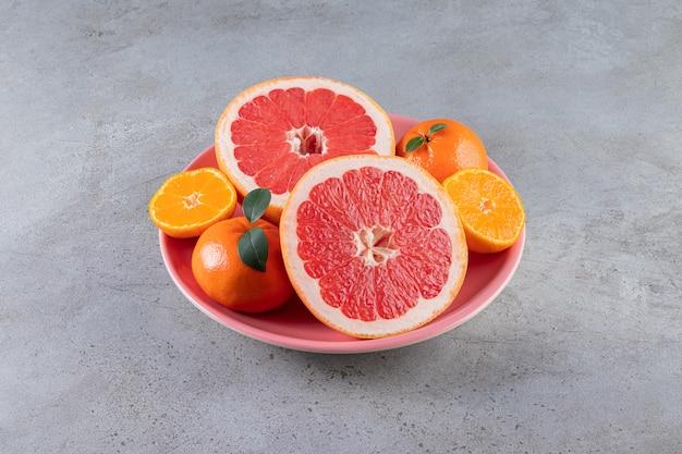 Segmenten van citrusvruchten, sinaasappel en grapefruitvruchten die op een plaat worden geplaatst.