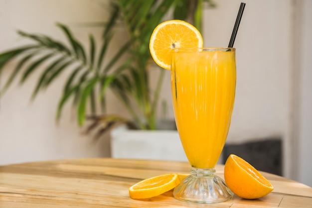 Segmenten van fruit in de buurt van glas drank met stro op tafel