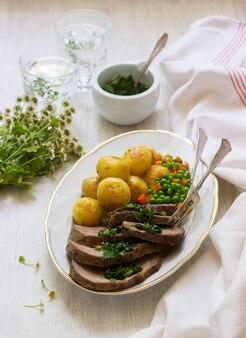 Segmenten van gebakken vlees met aardappelen en een garnering van erwten en wortelen op lichte ondergrond