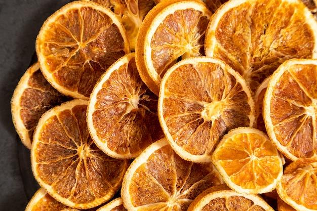 Segmenten van gedehydrateerde sinaasappel op zwarte steen. selectieve aandacht.
