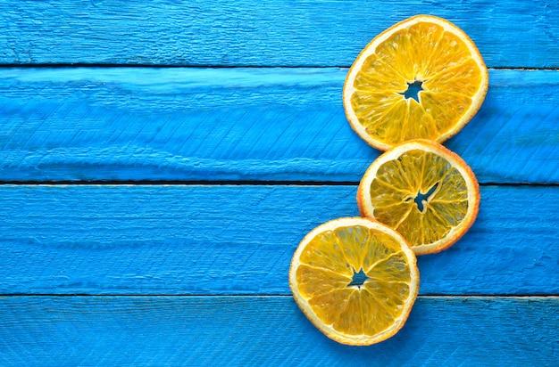 Segmenten van gedroogde oranje op blauwe houten planken. bovenaanzicht kopieer sace.