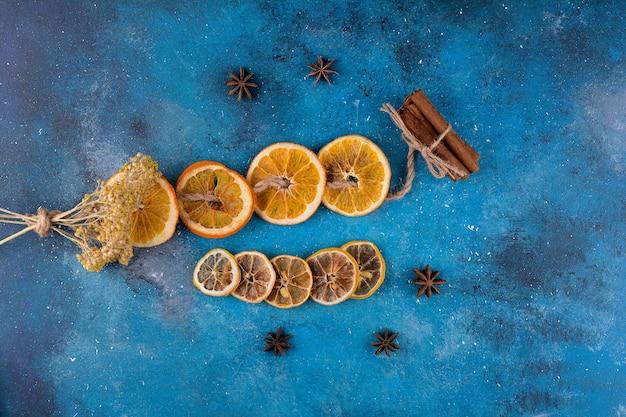 Segmenten van gedroogde sinaasappel met kaneelstokjes op blauwe tafel.