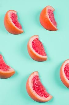 Segmenten van grapefruits op munt achtergrond