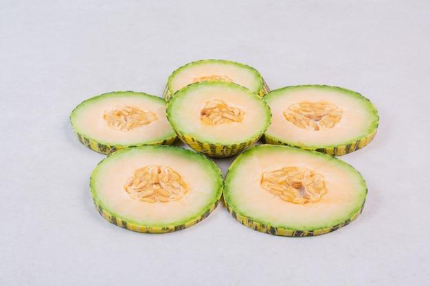 Segmenten van groene meloen op witte tafel.