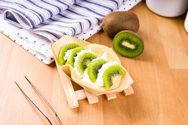 Segmenten van kiwi in een wafel op een houten en tafelkleed achtergrond. close-up