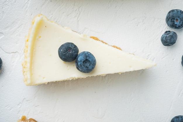 Segmenten van klassieke new york cheesecake, op witte tafel, bovenaanzicht plat lag