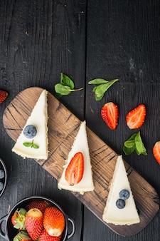 Segmenten van klassieke new york cheesecake, op zwarte houten tafel, bovenaanzicht plat lag