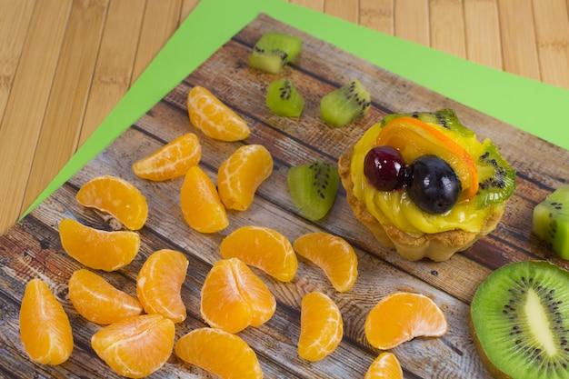 Segmenten van mandarijn, cake en kiwi. bovenaanzicht
