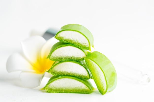 Segmenten van natuurlijke biologische aloë vera plant voor zelfgemaakte cosmetische lotion of olie tegen een witte achtergrond.