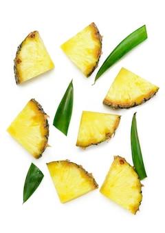 Segmenten van ongeschilde ananas en groene ananas bladeren op een witte isolaat.