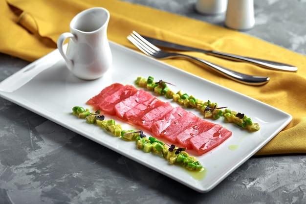 Segmenten van rauwe tonijn sashimi geserveerd op wit bord met avocado