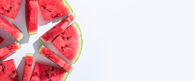Segmenten van rijpe watermeloen liggen op een witte achtergrond. bovenaanzicht, plat gelegd. banier.