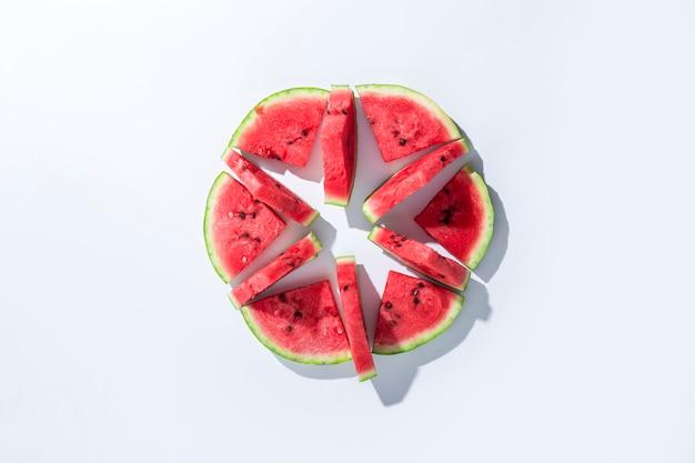 Segmenten van rijpe watermeloen liggen op een witte achtergrond. bovenaanzicht, plat gelegd.