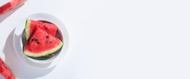 Segmenten van rijpe watermeloen op een bord op een witte tafel. bovenaanzicht, plat gelegd. banier.