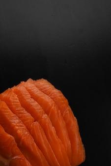 Segmenten van rode zoute rode zalm close-up. vers gezouten rode vis op een zwarte houten tafel met plaats voor tekst. natuurlijke omega-3 vitamine. kopieer ruimte. geweven macro-opname.