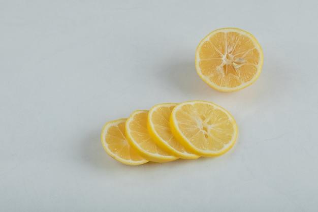 Segmenten van sappige citroen op een witte ondergrond.