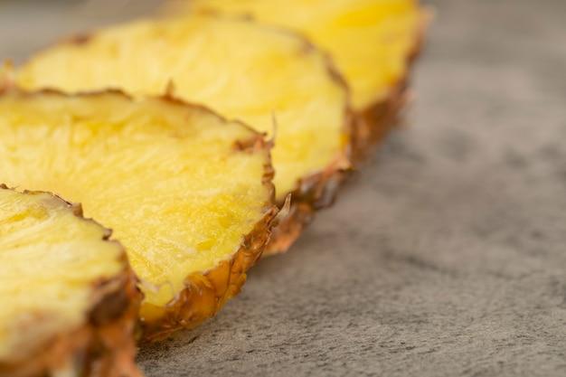 Segmenten van sappige heerlijke ananas geplaatst op stenen achtergrond.