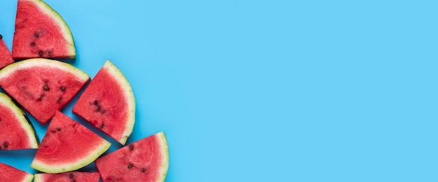 Segmenten van sappige rode watermeloen op blauw. bovenaanzicht, plat gelegd. banier.