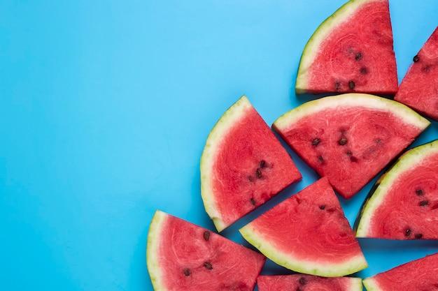 Segmenten van sappige watermeloen op een blauwe achtergrond. bovenaanzicht, plat gelegd.