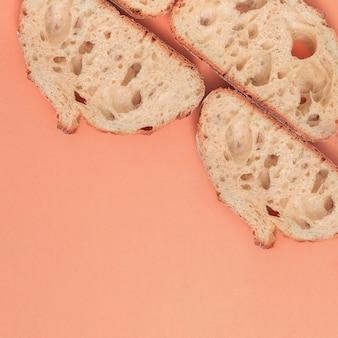 Segmenten van vers brood met kopie ruimte op perzik achtergrond