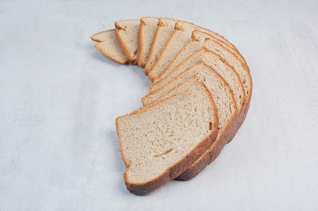 Segmenten van vers bruin brood op marmeren achtergrond.