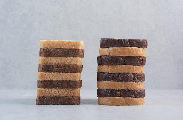 Segmenten van vers wit en bruin brood op marmeren achtergrond.