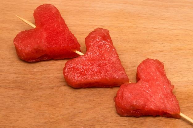 Segmenten van watermeloen, hart op houten achtergrond.