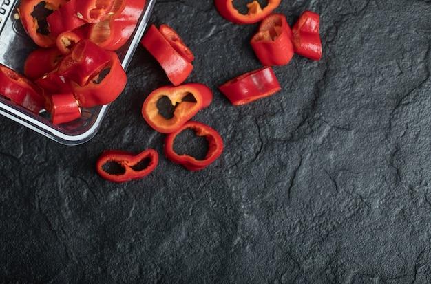 Segmenten van zoete rode paprika op zwart.
