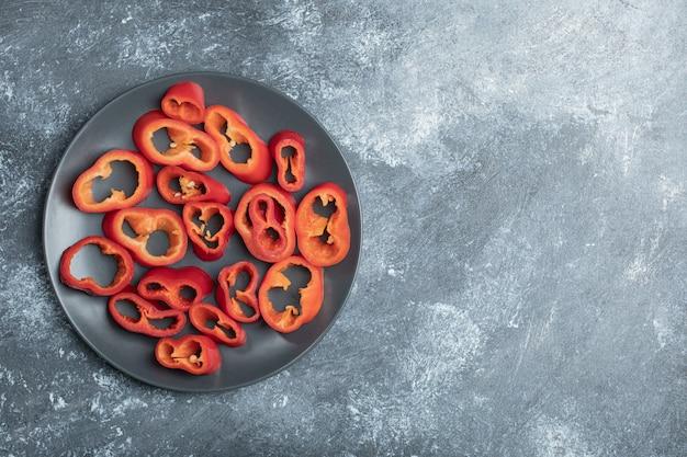 Segmenten van zoete rode paprika op zwarte plaat.